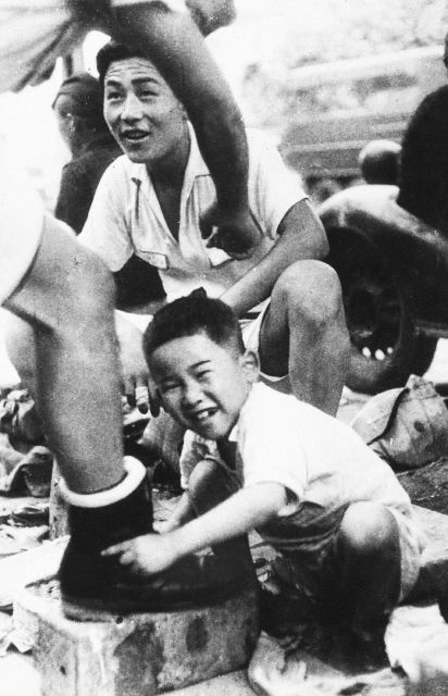 A war orphan polishes shoes in downtown Tokyo on Aug. 1, 1946. In Japan, war orphans were punished for surviving. They were bullied. They were called trash, sometimes rounded up by police and put in cages. Some were sent to institutions or sold for labor. They were targets of abuse and discrimination. A 1948 government survey found there were more than 123,500 war orphans nationwide. But orphanages were built for only for 12,000, leaving many homeless. (Kyodo News via AP)