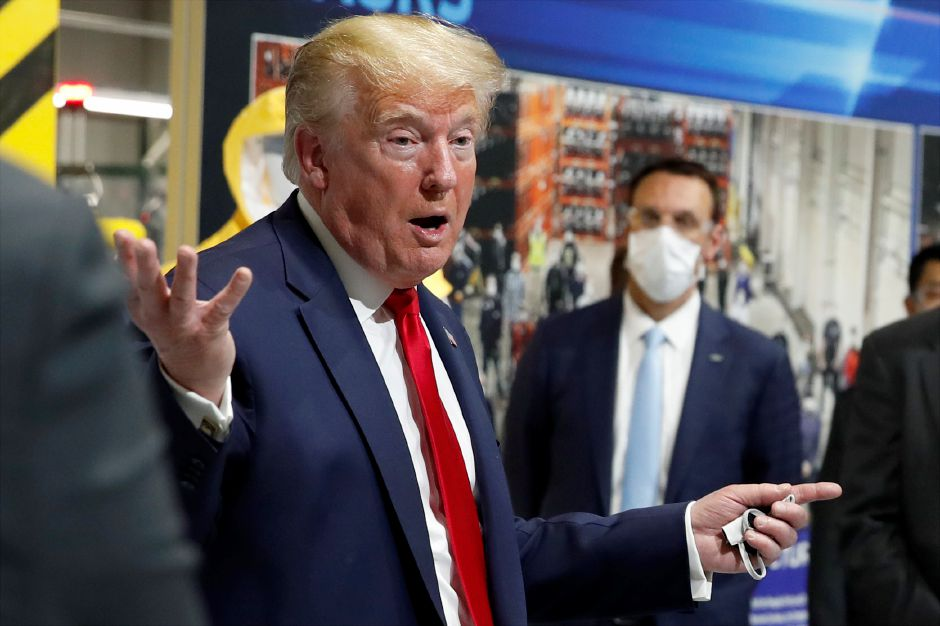 President Donald Trump holds a face mask in his left hand as speaks during a tour of Ford