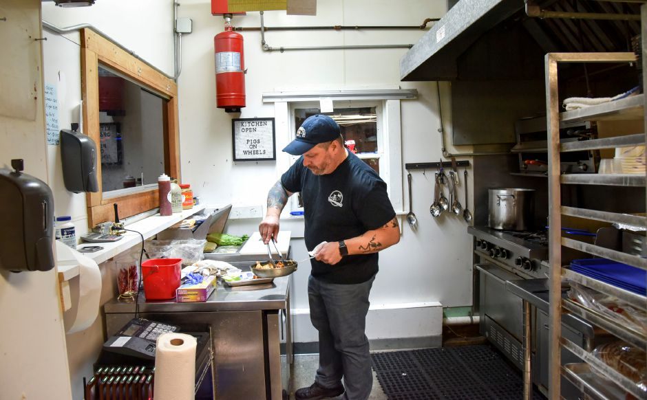 Matt Dube plates wings inside his new kitchen venture, Pigs on Wheels, in the Village Barn bar on River Road in Meriden, pictured on Dec. 3, 2019. Patrons can order food from inside the bar. | Bailey Wright, Record-Journal
