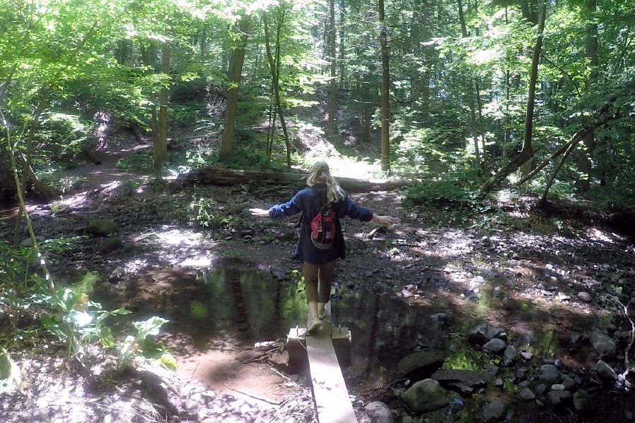Kristen Dearborn walks across a foot bridge constructed over a stream while hiking in Wallingford.