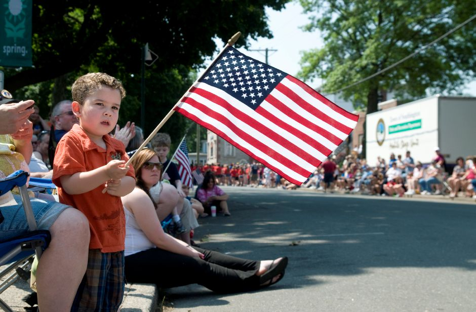 "Evan Wells,4, waves an American flag as he watches the Memorial Day parade on the Town Green in Southington, May 28, 2012. ""He comes from a big military family,"" said Patricia Tavalozzi, Wells"