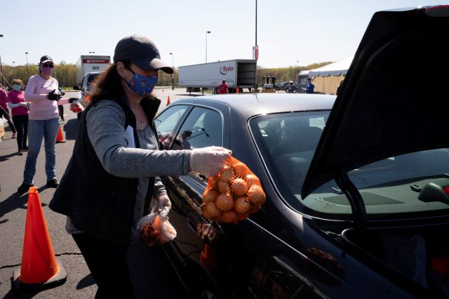 A volunteer loads a bag of onions into the trunk of a slowly moving vehicle at a Foodshare distribution center at Rentschler Field in East Hartford, Conn., Thursday, May 7, 2020, during the coronavirus pandemic. Foodshare has been offering the emergency drive-thru distribution for three weeks and said that as the lines continue to grow, they provide food to approximately 1,200 households per day. (AP Photo/Mark Lennihan)