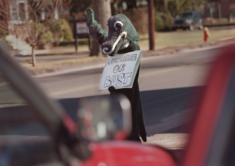"RJ file photo - Dressed in an alligator costume, Shawn Hebrank, 17, holds a sign, ""Lousiana or Bust"" as he waves to passing motorists in front of Vinny"