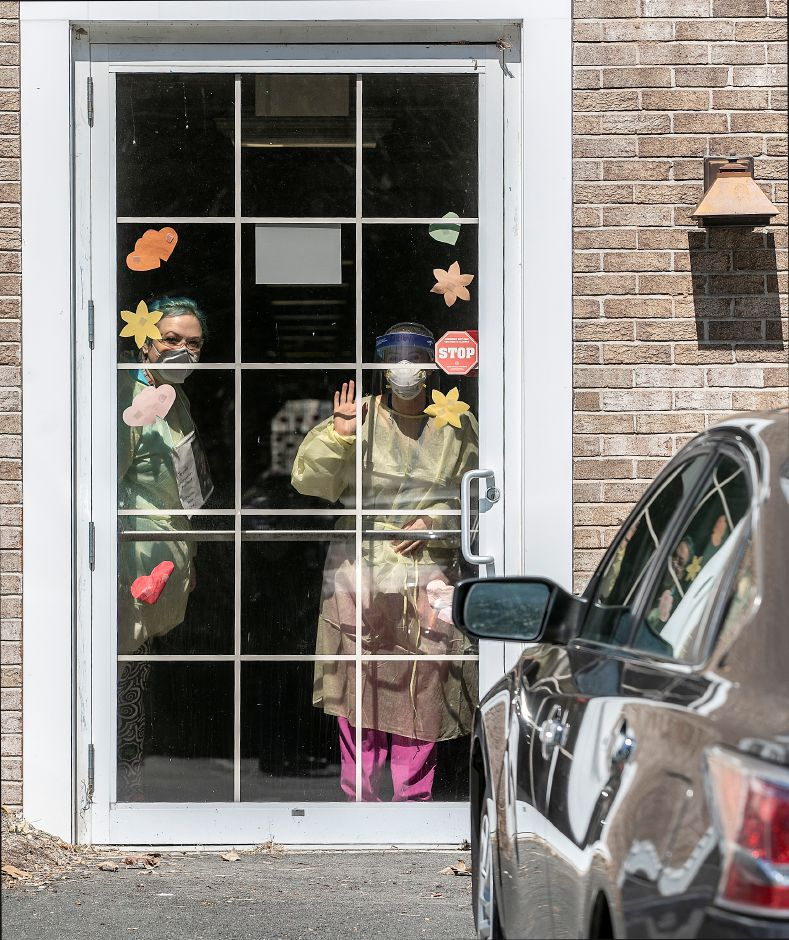 Workers wave from a door at Quinnipiac Valley Center, Wed., Apr. 15, 2020. The Connecticut National Guard is setting up more than 30 beds at the facility for recovering COVID-19 patients. The center is sixth on the state