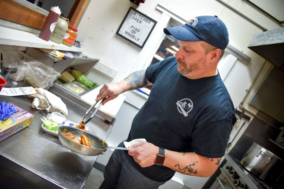 Matt Dube plates wings inside his new kitchen venture, Pigs on Wheels, in the Village Barn bar on River Road in Meriden on Tuesday. Patrons can order food from inside the bar.