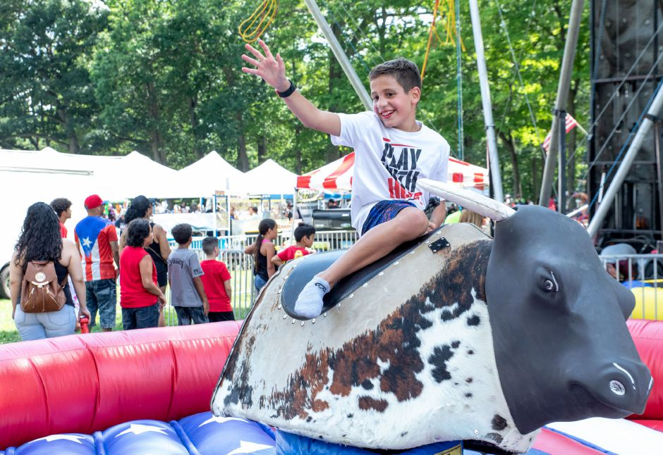 Lucas Rodriguez rides a mechanical bull during the Meriden Puerto Rican Festival at Hubbard Park on August 4, 2019. The city