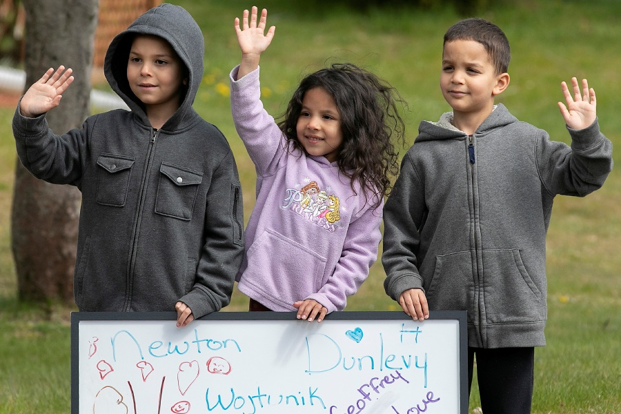 Students, left to right, Michael Geoffrey, 7, Cydney Geoffrey, 6, and Tristan Geoffrey, 6, of South Meriden, wave to teachers passing by during the Hanover School teacher parade on Main Street in South Meriden, Tues., Apr. 28, 2020. Dave Zajac, Record-Journal