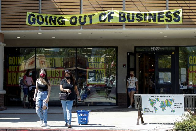 Shoppers walk outside of a Pier 1 Imports store as going out of business signs are posted amid the coronavirus pandemic Wednesday, July 1, 2020, in Santa Clarita, Calif. (AP Photo/Marcio Jose Sanchez)