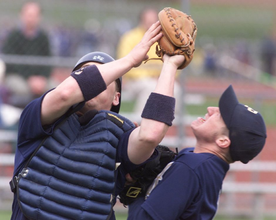 Platt catcher Ryan Laferriere hangs onto a pop-up as Platt pitcher Jason Morytko collides with him in foul territory for the last out of the top of the 1st inning in their game with Southington at Platt Wed., April 25, 2001. Southington scored 4-runs in the 1st inning.