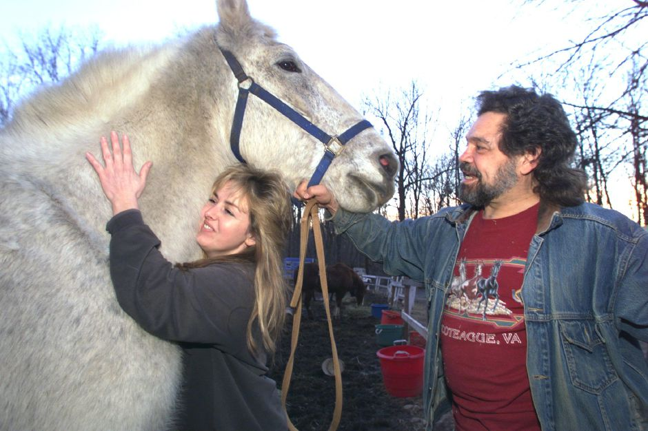 RJ file photo - Pixie Menchetti hugs an underweight Percheron horse while her husband Frank holds the reins. The Menchettis, who own Hidden Brook Horse Farm in Wallingford, rescue horses that have been neglected, Feb. 1999.