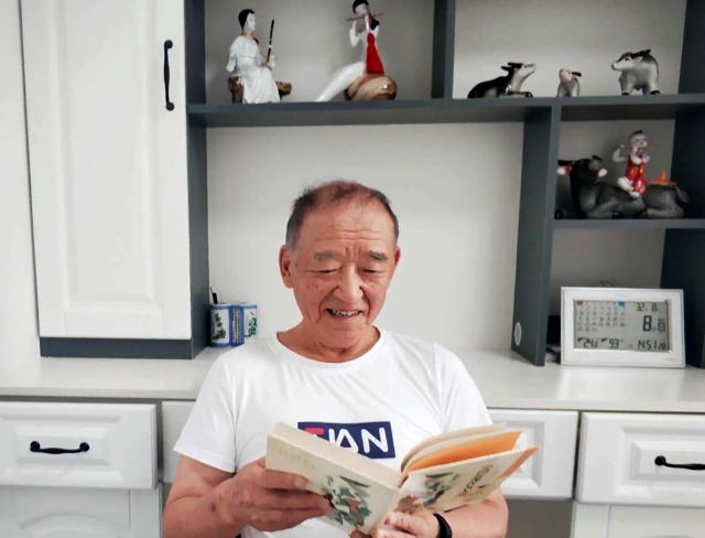 In this photo taken and released by Xi Chunmei, Xi Jingbo looks at a book at his new home in Linkou county, Mudanjiang city in northeastern China