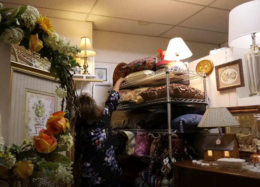 Owner Cindy Ruszczyk arranges pillows at Cindy