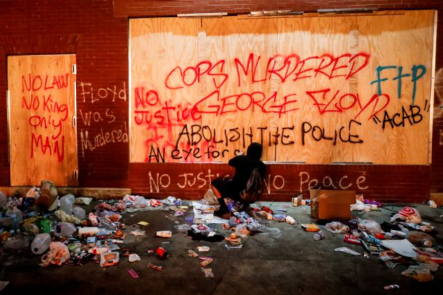 A protestor sprays graffiti on a wall near the Minneapolis 3rd Police Precinct, Thursday, May 28, 2020, in Minneapolis. Protests over the death of George Floyd, a black man who died in police custody Monday, broke out in Minneapolis for a third straight night. (AP Photo/John Minchillo)
