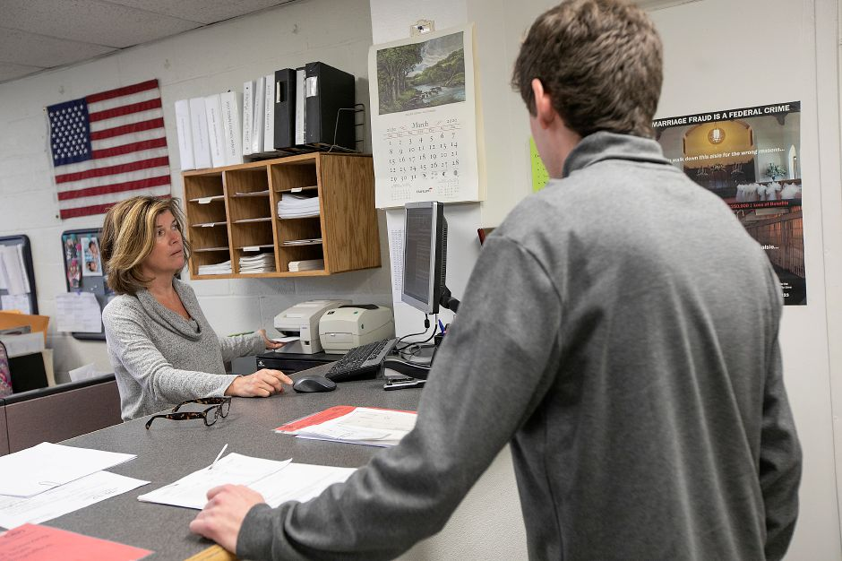 Town Clerk Barbara Thompson assists RJ Strollo, of Cheshire, in the Town Clerk office at Wallingford Town Hall, Mon., Mar. 16, 2020. Dave Zajac, Record-Journal