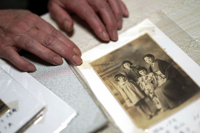 Mari Kaneda, 85, a WWII war orphan, shows a copy of family photo from year of 1944 during an interview with The Associated Press Sunday, July 19, 2020, in Warabi, north of Tokyo. In Japan, war orphans were punished for surviving. They were bullied. They were called trash, sometimes rounded up by police and put in cages. Some were sent to institutions or sold for labor. They were targets of abuse and discrimination. Now, 75 years after the war