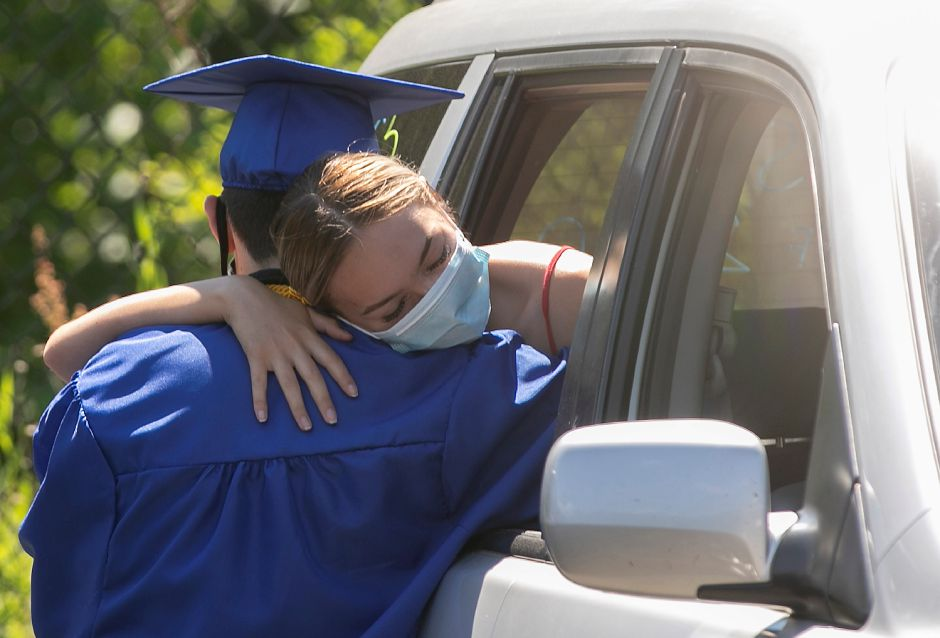Graduate Nathan DeMaio is hugged by girlfriend Mileni Flores after graduation ceremonies at  Wilcox Technical High School in Meriden Monday. Families watched the ceremony from their vehicles Monday afternoon.