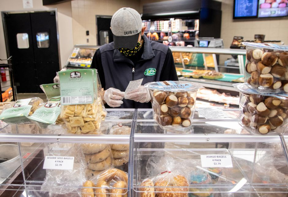 Chris Barra attaches the ingredients for the bagels that are pre-packed for customers at Tops Marketplace in Southington on June 30, 2020. Bagels and other food in the self-serve area have to be pre-packaged to help stop the spread of Covid-19. Aaron Flaum, Record-Journal