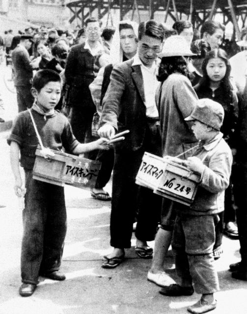 War orphans sell ice candy near Ueno station in Tokyo May 7, 1948. In Japan, war orphans were punished for surviving. They were bullied. They were called trash, sometimes rounded up by police and put in cages. Some were sent to institutions or sold for labor. They were targets of abuse and discrimination. A 1948 government survey found there were more than 123,500 war orphans nationwide. (Kyodo News via AP)