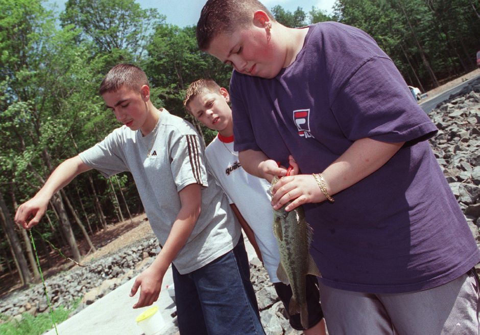 John Zappulla, left, 13, Anthony Russo, middle, 11, and Paul Fortin, right, 14, clean up their gear after several hours of fishing at Crescent Lake in Southington while one of their mothers wait in the parking lot to drive them home. The three boys are all cousins and live in Southington. Paul Fortin is removing a hook from the mouth of a one pound bass. This was at 3:12pm on Wednesday June 21, 2000.