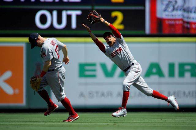 Boston Red Sox right fielder Mookie Betts, right, makes a catch on a ball it by Los Angeles Angels