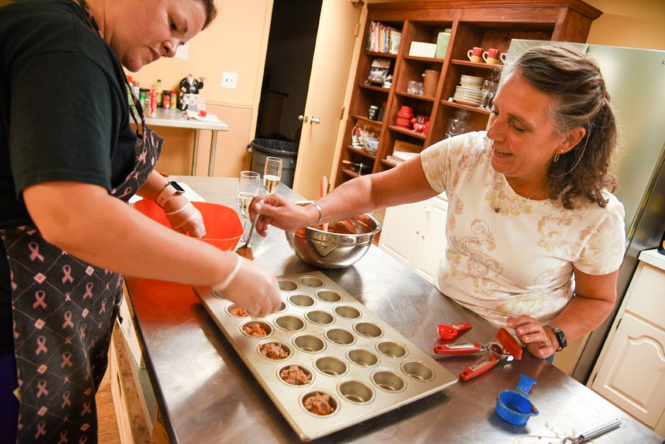 Participants fill muffin tins during a paleo-cooking class at the Meriden YMCA on Thursday, Sept. 19, 2019. | Bailey Wright, Record-Journal