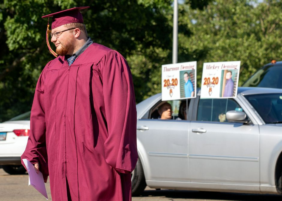 Sheehan graduate Mickey Daming watches his brother Thurman Daming receive his diploma Tuesday, June 23, 2020, during a drive up graduation at the school. Aaron Flaum. Record-Journal