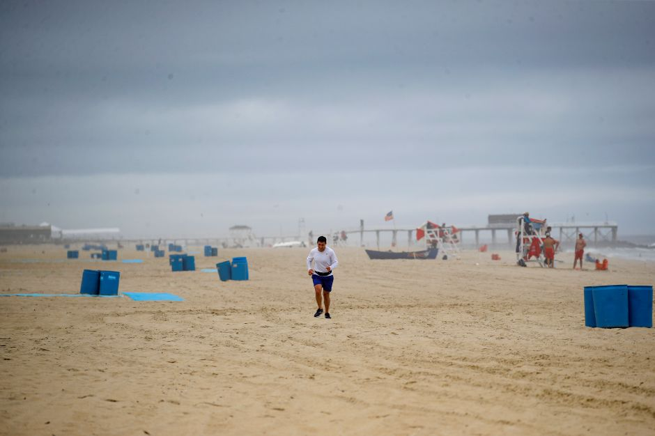 A runner passes along a mostly empty beach, Saturday, May 23, 2020, in Belmar, N.J. (AP Photo/John Minchillo)