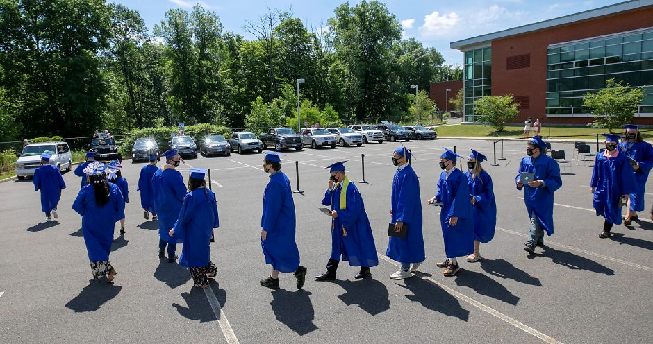 Electrical shop graduates walk in procession to awaiting parents honking horns in their vehicles after commencement ceremonies.