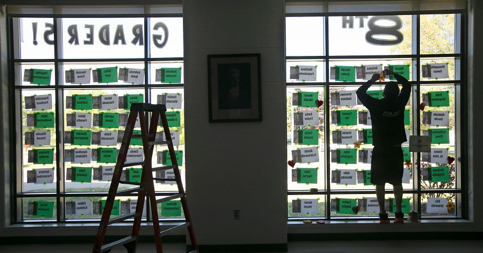 Paraeducator Mike Serafino adds a star to a tribute window for eighth-grade students at Kennedy Middle School in Southington, Thurs., May 21, 2020. The photos and names of more than 250 eighth graders, who are moving onto high school, now adorn the school