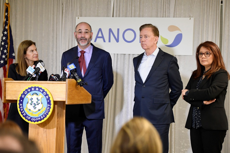 Clem Lewin, associate vice president of research and development strategy at Sanofi, speaks to the media as Lt. Gov. Susan Bysiewicz, Gov. Ned Lamont and Mireli Fino, site head at Protein Sciences, listen during a March visit to Protein Sciences in Meriden. | AP Photo/Jessica Hill.