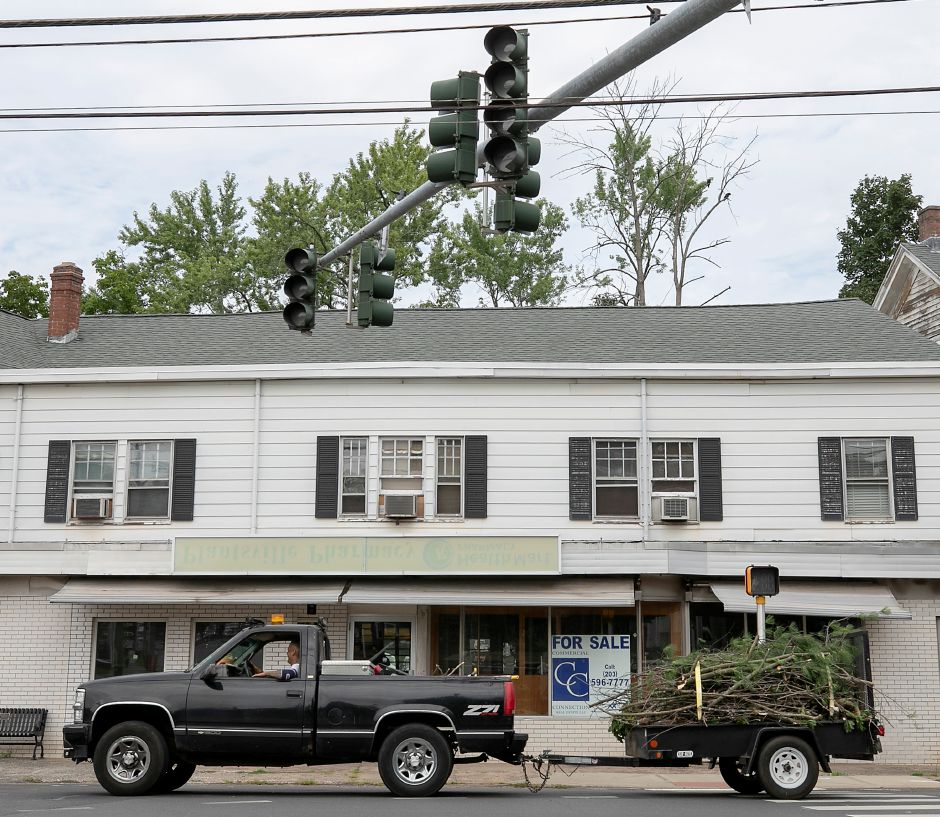Traffic lights remain out on West Main Street as a motorist tows a trailer of brush through the center of Plantsville, Thurs., Aug. 6, 2020. Thousands of residents in Cheshire, Southington and Meriden remained without power Thursday as state utilities drew criticism for the tropical storm response. Dave Zajac, Record-Journal