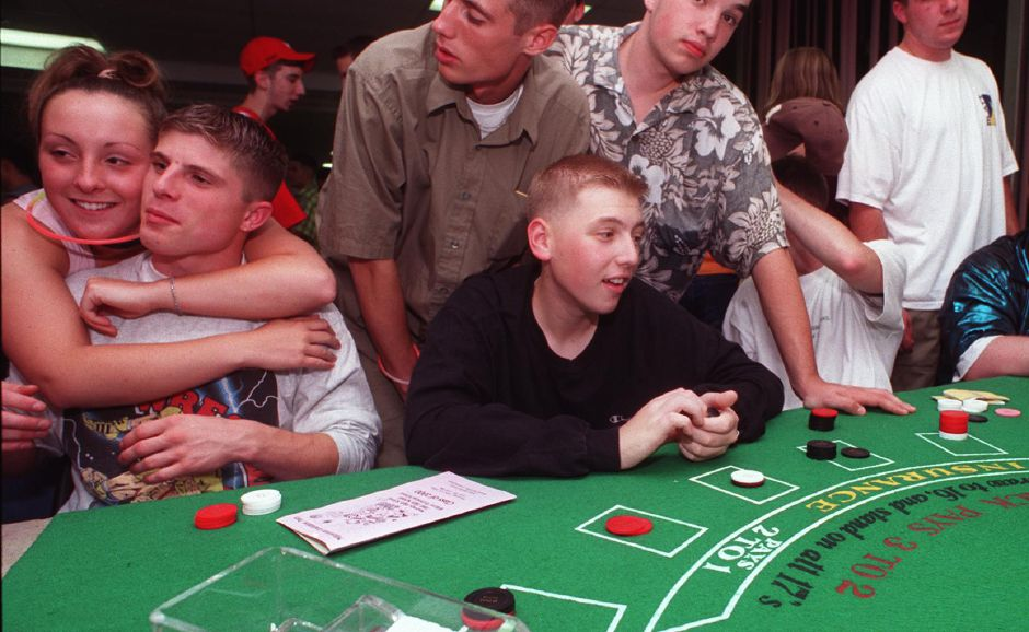 Ryan Post, left at table, and Dan Miller, at table with chips in hand, play a game of Poker while conversing with friends in the game room at Holy Angels Community Center at the tri-school graduation party Thursday night June 20, 2000.
