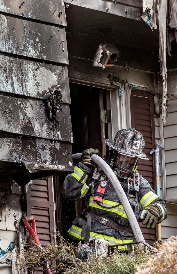 A Meriden firefighter gathers a hose on the front steps of a home heavily damaged by fire at 32 Spice Hill Dr., Monday morning, Sept. 28, 2020. Dave Zajac, Record-Journal