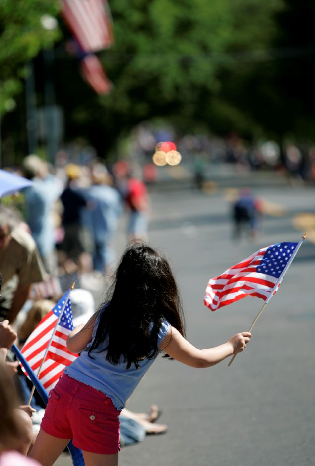 Sara Fallon, 7, a Meriden resident with her father and brother waves her American flag at the Memorial Day Parade participants as they approach marches down North Main Street before turning onto Center Street.| Record Journal Photo/ Johnathon Henninger 5.26.08