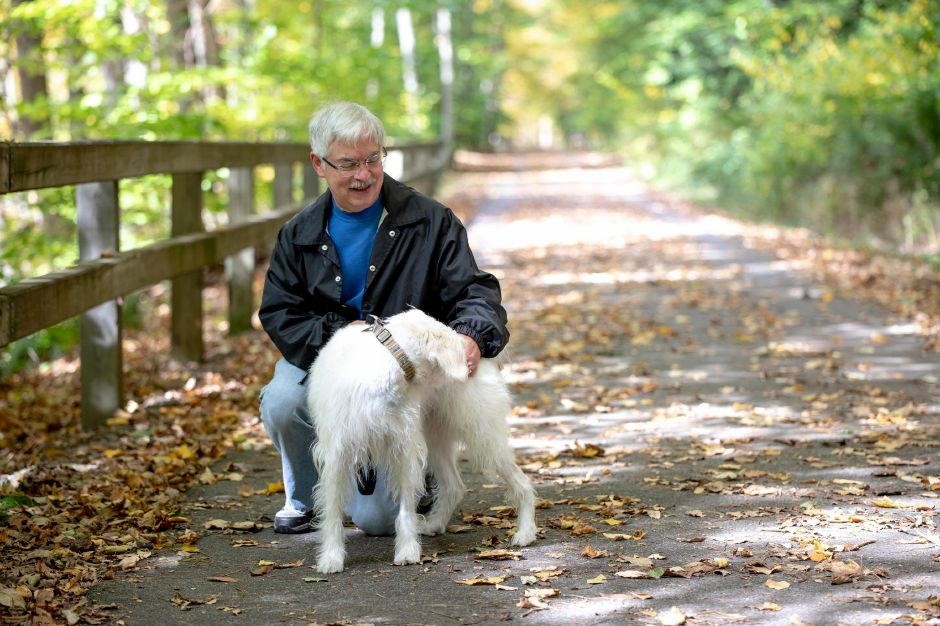 Meriden resident John Fama stops to pet his dog, Barney, while walking down the Quinnipiac River Linear Trail in Meriden on Sunday.  Devin Leith-Yessian, Record-Journal