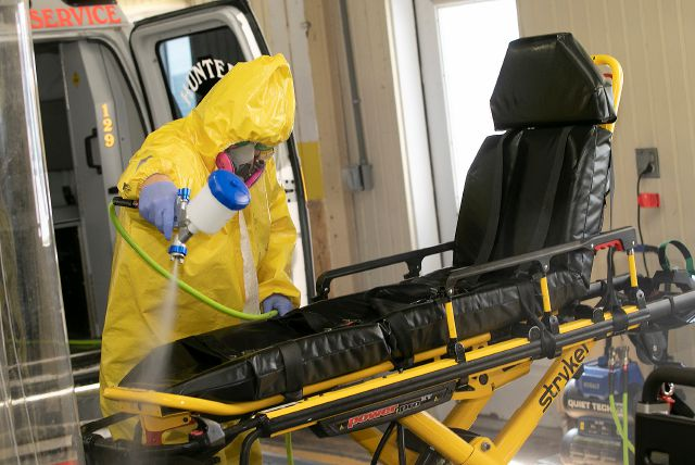 Decontamination team member Scott McMullen sprays down a stretcher with hydrogen peroxide to prevent the spread of the new coronavirus at Hunter