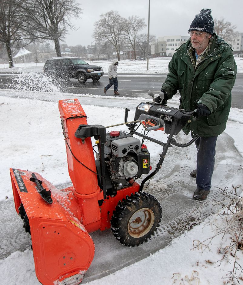 Joe Gibson, of Meriden, cleans up the sidewalk in front of his Twiss Street residence, Mon., Dec. 2, 2019. Dave Zajac, Record-Journal