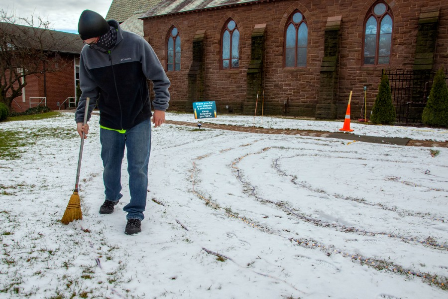 Robert Gervais, a church sexton at St. Paul's Episcopal Church in Wallingford, clears snow off the lights on the church's north lawn for the lighted labyrinth on Monday. The Lighted Labyrinth will continue through Wednesday, Jan. 6, 2021. For more information visit the church's website https://www.stpaulswallingford.org. Photos by Aaron Flaum, Record-Journal.com