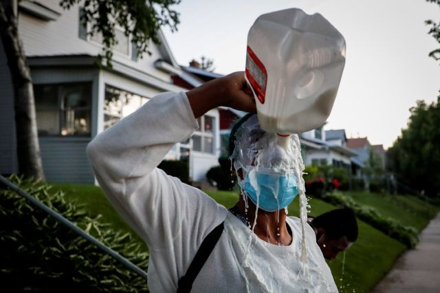 A protestor douses her face with milk after being exposed to tear gas fired by police, Thursday, May 28, 2020, in St. Paul, Minn. Protests over the death of George Floyd, a black man who died in police custody Monday, broke out in Minneapolis for a third straight night. (AP Photo/John Minchillo)