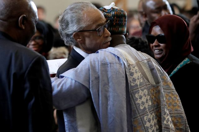 The Rev. Al Sharpton, center left, civil rights activist and founder of the National Action Network, hugs Imam Al Hassan Kamagtey, of Yonkers, N.Y., center right, as Omo Muhammed, right, mother of 19-year-old fatal shooting victim Mubarak Soulemane, looks on, Sunday, Jan. 26, 2020, during ceremonies to honor Soulemane