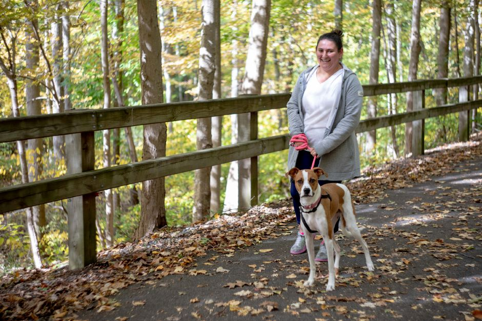 Meriden resident Nathalie Soucy and her dog Lucy walks down the Quinnipiac River Linear Trail in Meriden on Oct. 13, 2019. | Devin Leith-Yessian/Record-Journal