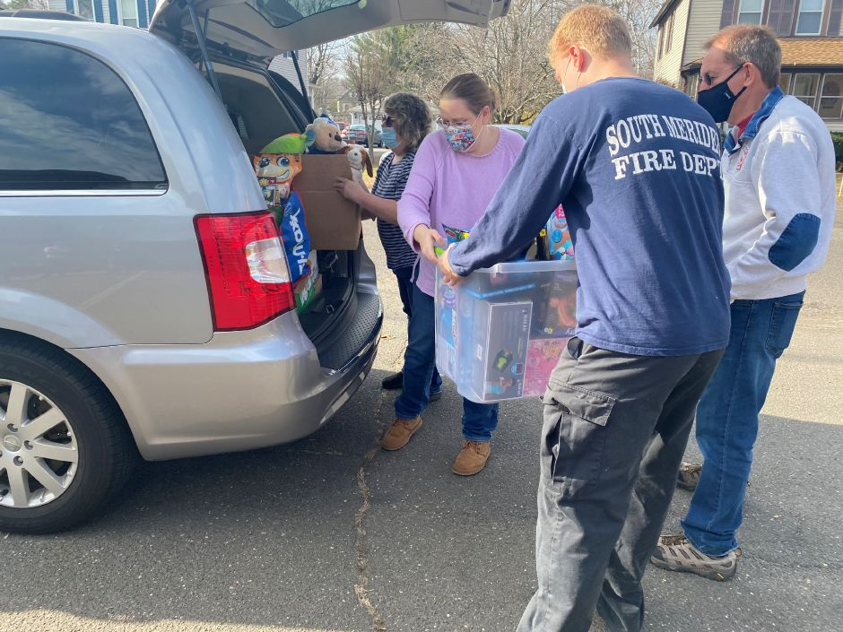 Laura Corchado, a Meriden resident, hands a tote to Ryan Larson, a SMVFD volunteer, full of toys to donate to South Meriden Neighborhood Associatons Turkey and Toy Drive on Saturday, Nov. 21. Faith Williams