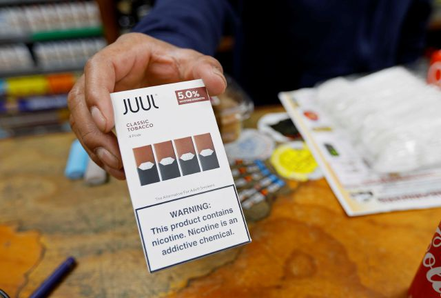 File - In this June 17, 2019, file photo, a cashier displays a packet of tobacco-flavored Juul pods at a store in San Francisco. Investigators from 39 states will look into the marketing and sales of vaping products by Juul Labs, including whether the company targeted youths and made misleading claims about nicotine content in its devices, officials announced Tuesday, Feb. 25, 2020. Juul released a statement saying it has halted television, print and digital advertising and eliminated...