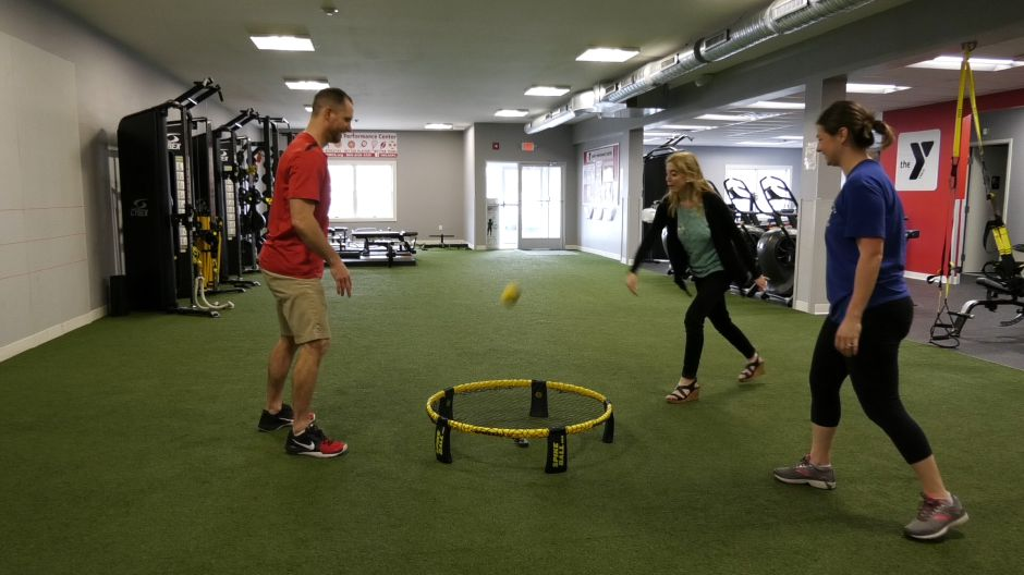 YMCA Sports Performance Director Thomas Sienkowski plays spikeball with Jacquelyn Seeger, membership director,  and Ashley Kus,  Record-Journal digital content producer, ahead of the  Connie J. Klanica Foundation spikeball tournament on Saturday, May 11, at the YMCA Camp Sloper Outdoor Center. Photos by Ashley Kus, Record-Journal