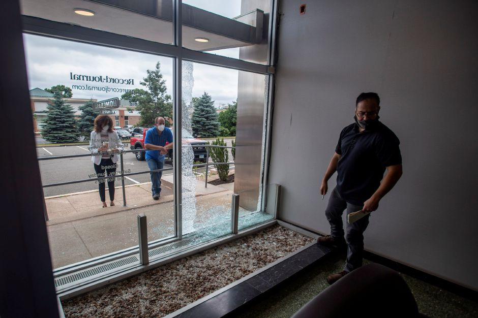 Meriden Police Detective John Femia looks over the broken glass after gunshots hit the building at 500 S. Broad St. Tuesday morning July 7, 2020. The building is home to several businesses, including the Record-Journal and The Money Source. | Richie Rathsack, Record-Journal staff