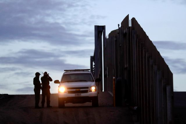 FILE - In this Nov. 21, 2018 file photo, United States Border Patrol agents stand by a vehicle near one of the border walls separating Tijuana, Mexico and San Diego, in San Diego. As of this week, the ACLU has filed nearly 400 lawsuits and other legal actions against the Trump administration, some meeting with setbacks but many resulting in important victories. Of the lawsuits, 174 have dealt with immigrant rights, targeting the family separation policy, detention and deportation...