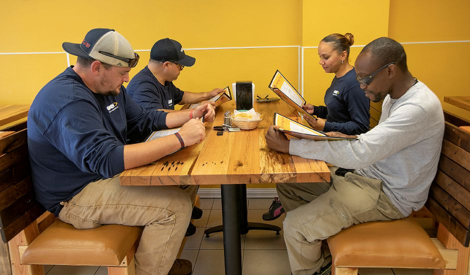Left to right, Adam Chamberlain, Pete Flores, Omaira Agudo and Terrence Agudo, look over menus at Hashtag Tacos on Main Street in Yalesville while on their lunch break from GKN Aerospace in Wallingford, Thurs., Sept. 12, 2019. Hashtag Tacos serves appetizers, platters and a variety of tacos. Dave Zajac, Record-Journal