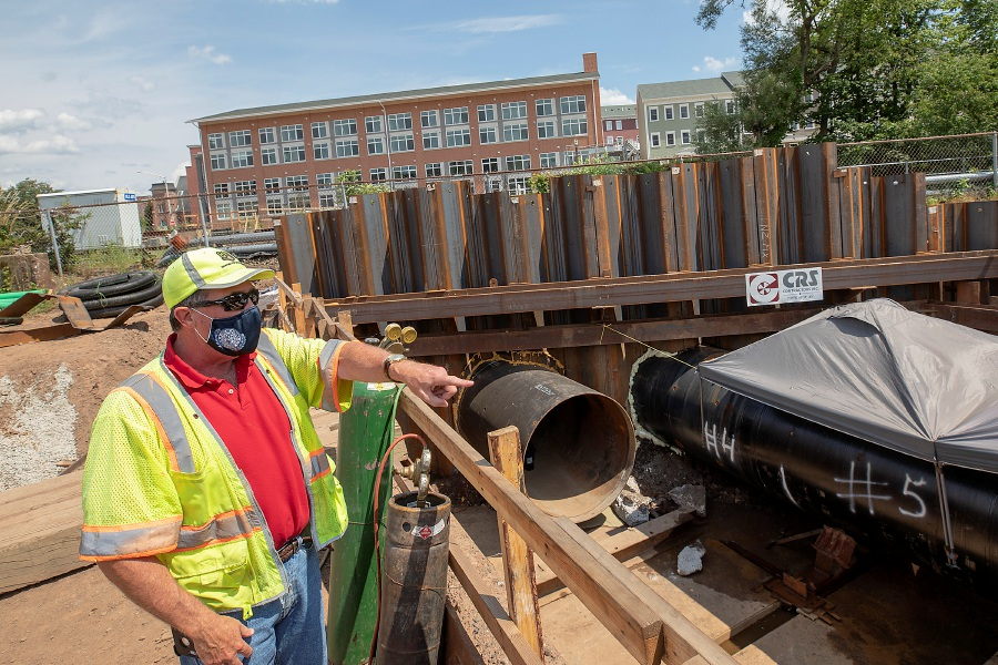 "Associate City Engineer Brian Ennis talks about the installation of two large steel pipes for flood control in downtown Meriden, Thurs., Jul. 30, 2020. The city is installing the pipes under the railroad tracks near the former Church & Morse building on South Colony Street to fix what officials say is a main choke point along Harbor Brook and the origin of many past floods. The drainage pipes are being pushed underneath the tracks at the ""Amtrak Bridge"" to drain excess water in the event of a storm. The bridge is located off Hanover Street, behind the police station parking lot. Dave Zajac, Record-Journal"