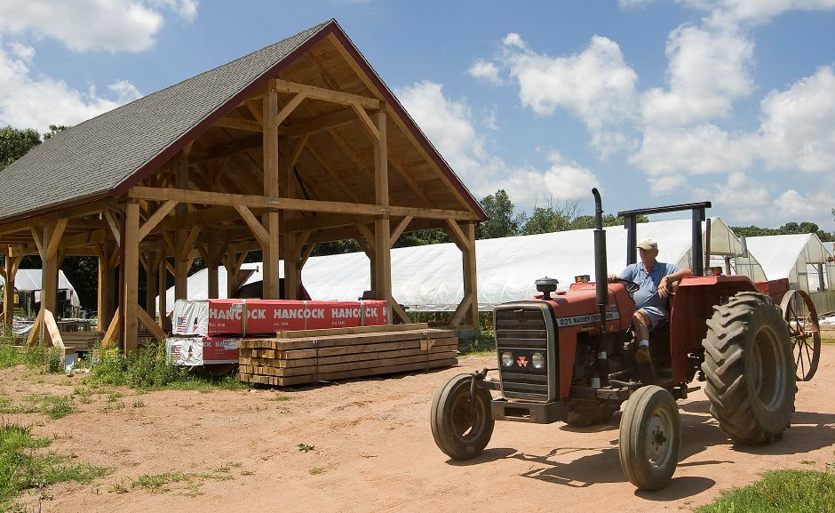 Doug Yocher of Cheshire drives past a new barn being constructed for the Cheshire Land Trust at 1585 Cheshire Street in Cheshire, Friday, July 5, 2013. Yocher is a worker for T & D Growers which operates on the farm acquired by The Cheshire Land Trust in August 2006. (Dave Zajac/Record-Journal)