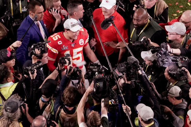 FILE - In this Feb. 2, 2020, file photo, Kansas City Chiefs quarterback Patrick Mahomes (15) is surrounded by media after his team won the NFL Super Bowl 54 football game against the San Francisco 49ers, in Miami Gardens, Fla. As sports prepare to resume, journalists are facing the same reckoning that their colleagues who cover politics, education and entertainment have encountered — coming up with new approaches to coverage with reduced access and resources. Professional leagues closed...